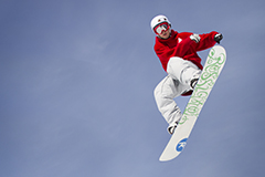 Snowboarder in the air after jumping off a rail.